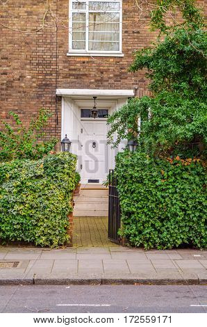 the entrance to a building stone steps on botj sides green vegetation white window peak at the entrance two stylish lamps on both sides of the entrance a beautiful white wood doors brick wall