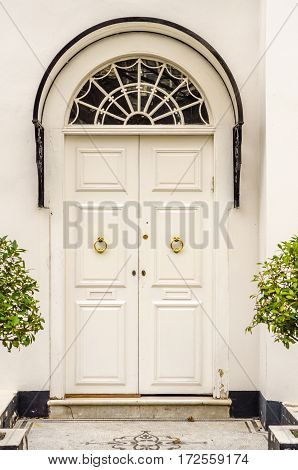 stylish entrance to the building with characteristic arches with hood a white wooden door with golden knockers before the two pots of exotic plants floor paved with the door with decoration elegant entrance