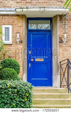 the entrance to a building stone steps on the right side of the metal railing on the left side of lush green vegetation small white box peak at the entrance two stylish lamps on both sides of the entrance a beautiful blue wood doors brick wall