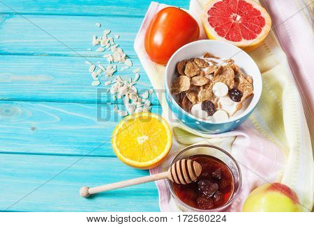 Bowl of healthy corn flakes breakfast cereal milk and fruits on blue wood table.