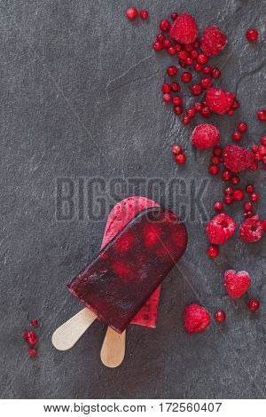 Ice cream lollies and frozen fruit on  dark background, top view, copy space