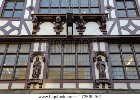 WINCHESTER, UK - FEBRUARY 4, 2017: Exterior facade with wooden statues in the busy and commercial High Street