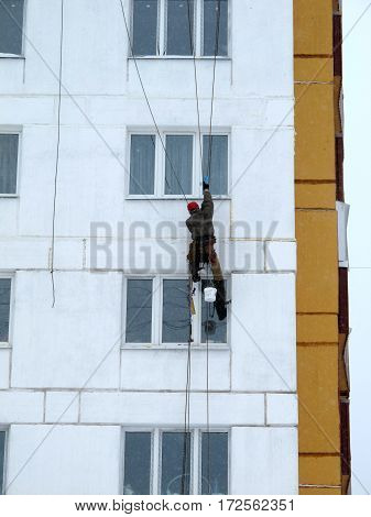 Industrial climber in helmet and uniform puttying wall on height. Risky job. Extreme work. Worker alpinist.