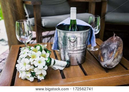 Bottle of champagne in bucket, glasses with frangipani and old mago fruit on a wooden chair