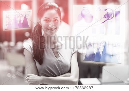 Graph against happy businesswoman standing with arms crossed