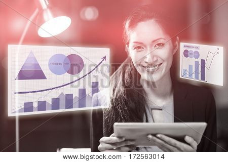 Graph against businesswoman holding digital tablet