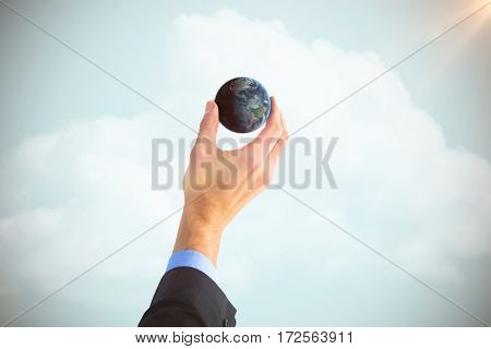 Businessman holding little earth in presentation against blue sky