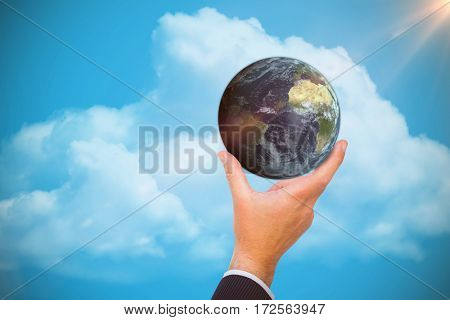 Businessman presenting earth with his finger against blue