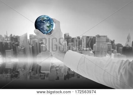 Businessman holding hand out little earth in presentation against new york