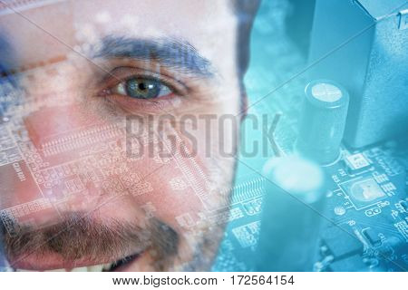 Man with green eyes against micro parts in mother board