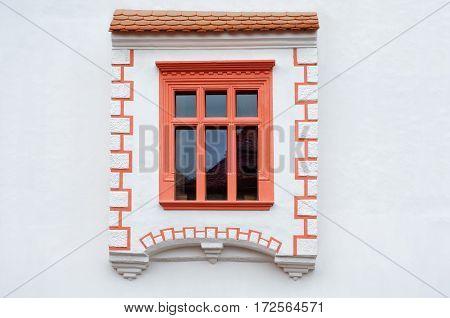 Rustic red window on white wall in Sighisoara Romania