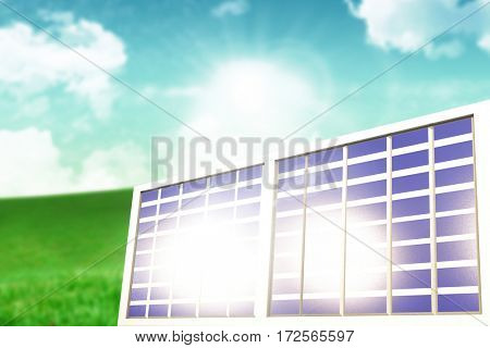 Illuminated solar panel against green field under blue sky