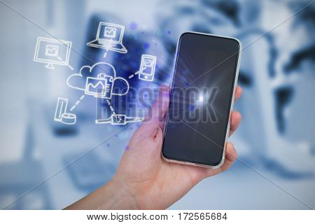Hand holding mobile phone against white background against computers and headsets