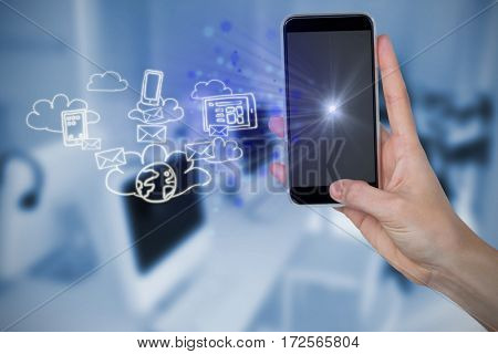 Human hand holding mobile phone against white background against computers and headsets