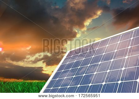 Solar panel with hexagon shape glasses against green grass under dark blue and orange sky