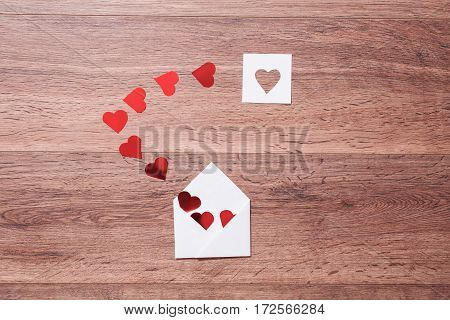 Greeting card. Conceptual photography. Wedding invitation card. Valentine day. Red hearts in envelope on wooden background. Flat lay top view copyspace
