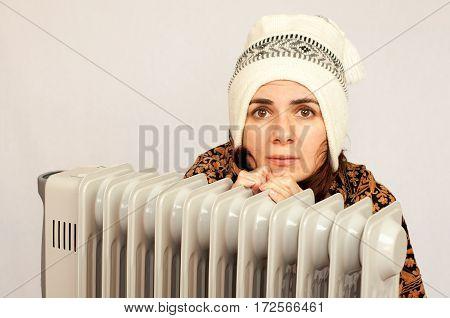 Young woman freezing near the heater studio shot