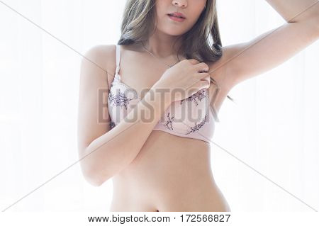 Young woman in lingerie raising up her arms and showing her armpits
