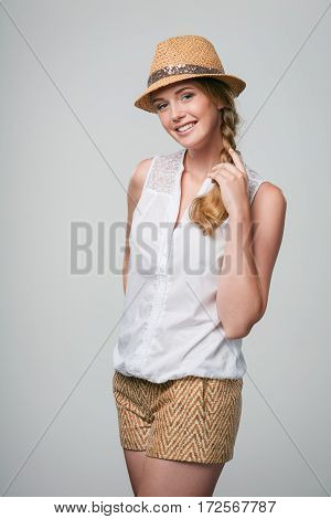 Happy woman wearing summer straw fedora smiling at camera playing with her braid