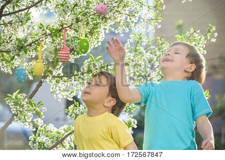 Two little friends in Easter hunting eggs in spring garden outdoors. On warm sunny day with blooming trees on background.