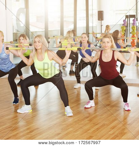Group of young women in fitness class making exercises. Girls do squats with barbells. Healthy lifestyle, training with weights.