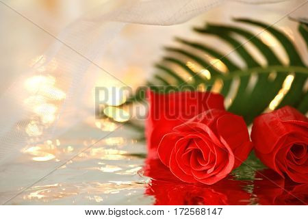 Red roses and a green leaf with reflection under a white wedding veil. Space for text