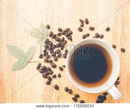 coffee bean and coffee mug on wood background