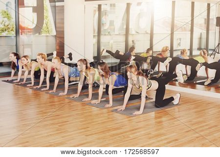 Group of young women in fitness class making slimming workout. Girls do donkey leg kick exercise. Healthy lifestyle in sport club, weight loss training