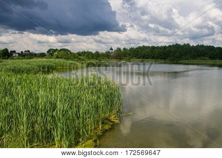 Green countryside landscape reflection in lake with blue cloudy sky background