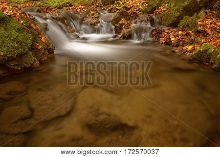 Detail of autumn brook with rocks and leaves. Long exposure for smooth water flow