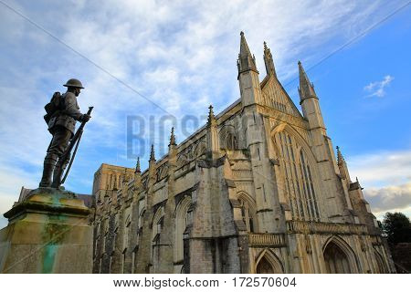 WINCHESTER, UK - FEBRUARY 4, 2017: Exterior view of the Cathedral with the statue of First World War Soldier in the foreground