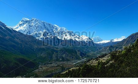 Panoramic view of covered with snow Himalayan Mountains Nepal. View of Manang village valley river and airport. Way to Thorung La pass and Tilicho Lake from Annapurna Circuit Trek Nepal. poster
