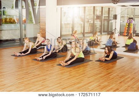 Group of young women in yoga class making exercises. Girls do leg stretching. Healthy lifestyle in fitness club. Head to knee pose.