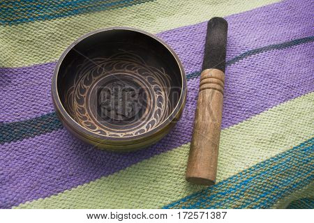 Tibetan singing bowl with stick on the background of linen Mat