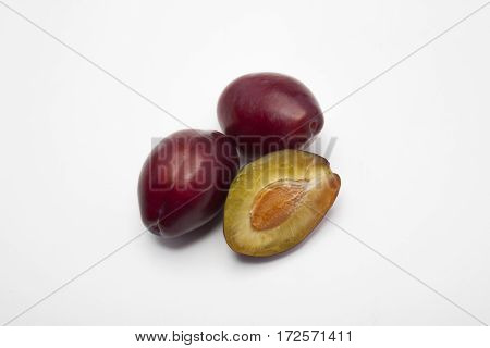 Three plums on a white background. Three juicy blue plum plum