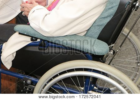 Symbol Of The Old Age Of The Population A Wheelchair With An Elderly Woman