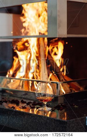 A glass of cognac on oak table on the background of a burning fireplace