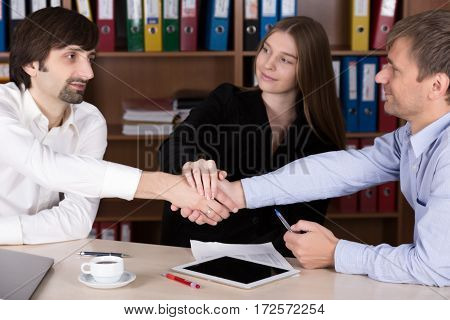 Three Business People Men and Lady shaking Hands after reaching a Deal in Office Interior with many color Document Folders on Background Focus on Hands