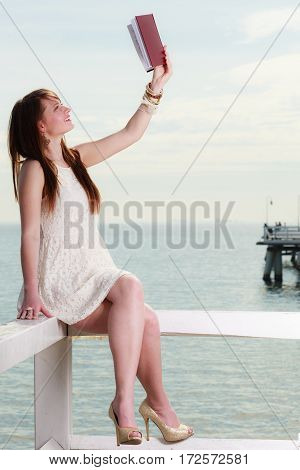 Books bookworm travel leisure time concept. Beautiful woman wearing white dress sitting on wooden hurdle near sea and book in the air