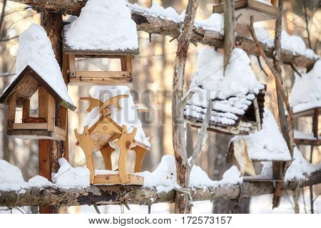 Group of wooden bird feeders tree houses in winter forest