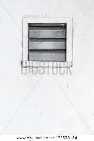 Air ventilation frame on the white wall of the small factory.