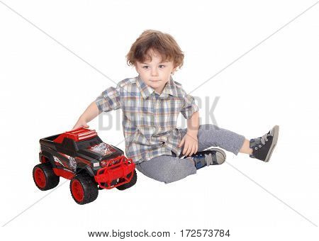 A lovely three year old boy sitting on the floor playing with his monster toy track isolated for white background.