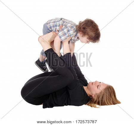 A mother lying on the floor holding her little three year old boy up on her feet in the air isolated for white background.