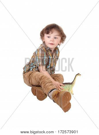 A beautiful three year old boy sitting on the floor playing with his toys isolated for white background.