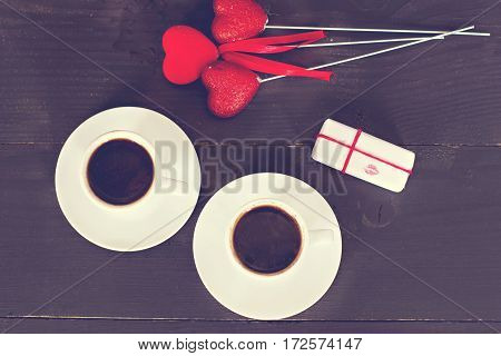 cups of espresso coffee and hearts card on Valentine's Day gift surprise. Dark background space for text.