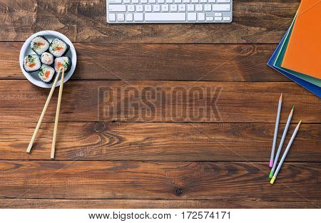 Top View of Vintage handmade Wood Table with Business and Lifestyle Items Computer Keyboard Color Pencils Documents Asian Sushi Set with Chopsticks on Desk