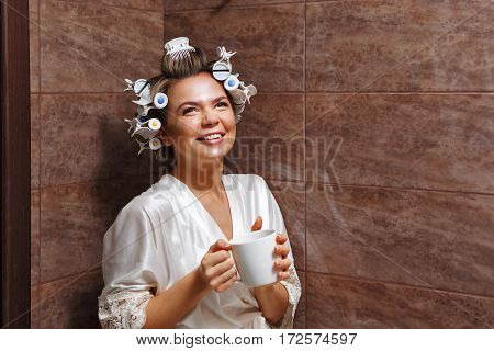 Young attractive housewife in the bathroom. Girl in a bathrobe and curlers drinking morning coffee. Good morning. Hot drink. Dreaming.