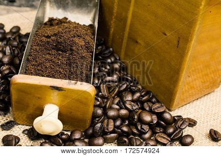 Espresso beans in an old coffee mill on a rustic background