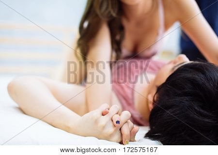Young Couple Holding Hands While Making Love With Affection On Bed - Sex Concept