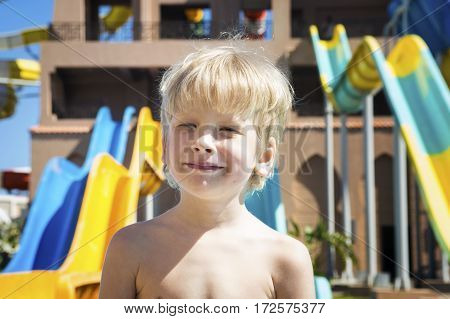 Portrait of the smiling boy against the background of aquapark
